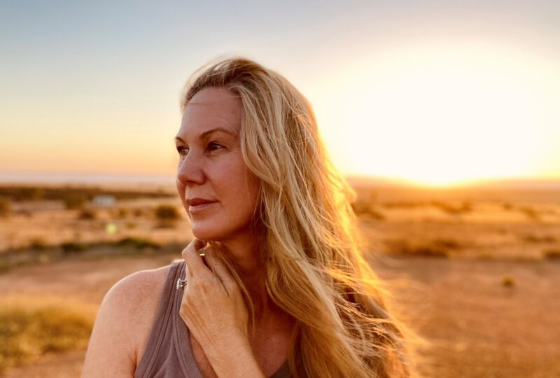 Lynda Howitt standing in a field. Lynda has long blonde hair and is wearing a grey singlet. She is looking into the distance and holding her arm is crossed over so her hand sits under her chin. The image is backlit with golden light.